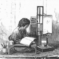Person studying a book at a desk